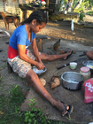 Young Fijian woman cooking Gnau Fiji