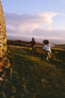 Children running Celtic circle Grianan of Aileach Donnegal Ireland